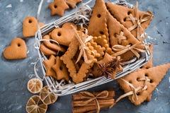 Julkryddor, pepparkakakakor och stekheta ingredienser på grå färger hårdnar bakgrund Kanel anisstjärnor, muskotnöt, cardamon, Royaltyfri Bild