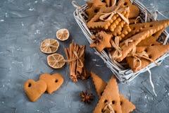 Julkryddor, pepparkakakakor och stekheta ingredienser på grå färger hårdnar bakgrund Kanel anisstjärnor, muskotnöt, cardamon, Royaltyfri Fotografi