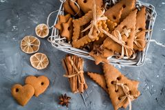 Julkryddor, pepparkakakakor och stekheta ingredienser på grå färger hårdnar bakgrund Kanel anisstjärnor, muskotnöt, cardamon, Arkivfoto