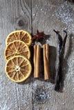 Julkryddor, torkade orange skivor, kanelbruna pinnar, stjärnaanis, vaniljbönor på träbakgrund Fotografering för Bildbyråer