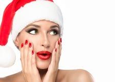 Julkvinna i den isolerade jultomtenhatten med ett överraskninguttryck Arkivbilder