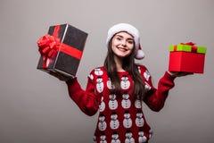Julkvinna med gåvaaskar Den härliga brunettflickan som bär i tröja och Santa Hat, isolerade Royaltyfri Foto