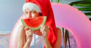 Julkvinna som äter vattenmelon i baddräkt Arkivfoto
