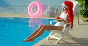 Julkvinna som äter vattenmelon på pölen Royaltyfri Foto