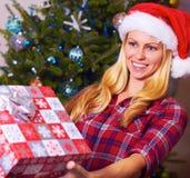 Julkvinna som ger gåvan Fotografering för Bildbyråer