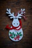 Jullandskap En vit älg med den röda teckningen mot en mörk bakgrund Arkivfoton