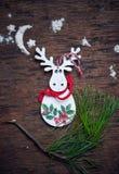 Jullandskap En vit älg med den röda teckningen mot en mörk bakgrund Royaltyfri Foto