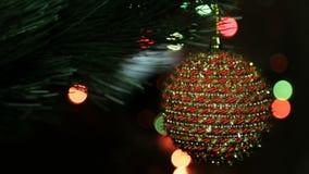 Julleksak på en julgran mot en girland i suddigheten lager videofilmer