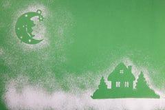 Julleksaker, handgjord trämånestjärna och hem, på en grön bakgrund royaltyfria foton