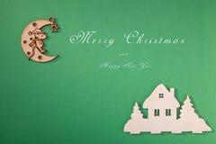 Julleksaker, handgjord trämånestjärna och hem, på en grön bakgrund arkivfoton