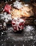 Julleksaker i form av gåva- och vintergarneringar på lantlig träbakgrund Royaltyfri Foto