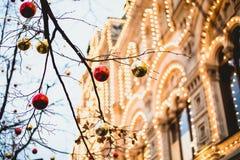 Julleksaker på en trädfilial med bakgrund tänder royaltyfri foto