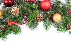 Julleksaker på granträdfilialen som isoleras på royaltyfri foto