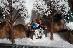 Julleksakgarnering tjusade parsammanträde på en träbänk och att sjunga från en varm drink för termos på naturen nära ett träd fotografering för bildbyråer