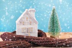 Julleksakhus som slås in i varm halsduk och grönt Xmas-träd arkivbilder