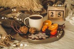 jullivstid fortfarande Träkalenderuppsättning för gammal tappning på 25na av December med koppen med te, kakor, apelsiner och mut royaltyfria foton