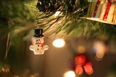 Julljus, grönt träd och vitsnögubbe med den svarta hatten Arkivfoton