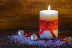 Julljus med röda pilbåge- och bollgarneringar på snö Arkivbild