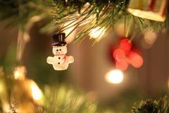 Julljus och grönt träd med den lilla snögubben Arkivfoto