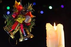 Julljuset bränner Nära de gröna filialerna av granen och klockor lyckligt nytt år arkivfoton