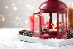 Jullykta med stearinljus, snö, julgarneringar och grankottar Arkivfoto
