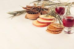 Julmatbakgrund - funderat vin Dekorativ garnering av kryddor och drinkar på den vita trätabellen Fotografering för Bildbyråer