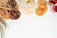 Julmatbakgrund - funderat vin Dekorativ gräns av kryddor och drinkar på det vita wood brädet Arkivbild