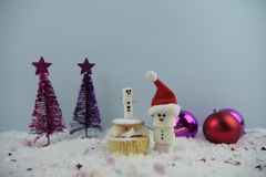 Julmatfotografi genom att använda marshmallower som formas som snögubben och anseende i snö med kakan och struntsaker för kräm- s Royaltyfri Foto
