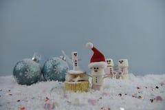 Julmatfotografi genom att använda marshmallower som formas som snögubben och anseende i snö med kakan och struntsaker för kräm- s Royaltyfri Fotografi