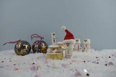 Julmatfotografi genom att använda marshmallower som formas som snögubben och anseende i snö med kakan och struntsaker för kräm- s Arkivbild