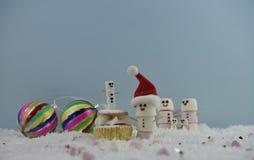 Julmatfotografi genom att använda marshmallower som formas som snögubben och anseende i snö med kakan och struntsaker för kräm- s Arkivfoton