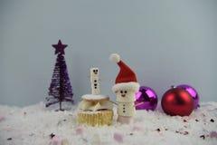 Julmatfotografi genom att använda marshmallower som formas som snögubben och anseende i snö med kakan och struntsaker för kräm- s Arkivbilder