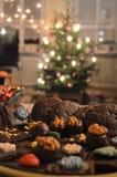Julmellanmål och ccokies i en bunke framme av julträdet arkivfoton