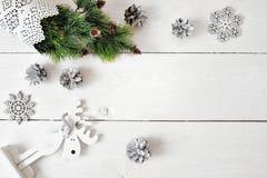 Julmodell på en vit träbakgrund med snöflingor, en hjort och en julgran Lekmanna- lägenhet, bästa sikt Arkivbild