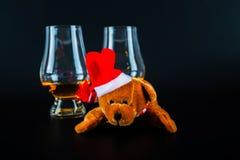 Julnallebjörn med exponeringsglas av enkel maltwhisky, symbolnolla Arkivfoton