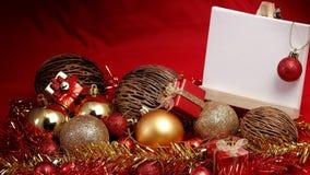 Julobjekt i rött och guld- tema med anseendet för det vita brädet för skriver formuleringar Royaltyfri Foto