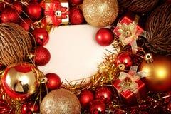 Julobjekt i rött och guld- tema med den vita ramen för skriver ord Royaltyfri Bild