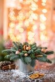 Julordningen med norrman sörjer Nobilis och som dekorerar med juldekoren i en metallkopp Girlandbokeh på arkivfoto