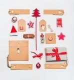 Julorientering med pappers- slående in gåvaaskar för hantverk, etiketter, kakor, röd feriegarnering, gåva, kryddor, jultomtenhatt Royaltyfri Bild