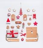 Julorientering med pappers- slående in gåvaaskar för hantverk, etiketter, kakor, röd feriegarnering, gåva, kryddor, jultomtenhatt Fotografering för Bildbyråer