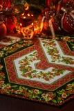 Julpatchworkservett, julstearinljushållare med den inre flammande stearinljuset och julgarneringar som är suddiga på tillbaka sik fotografering för bildbyråer