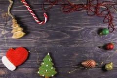 Julpepparkakakakor, dekor och godis på en träbakgrund Fotografering för Bildbyråer