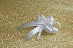 Julpilbåge på bakgrund i guld Arkivfoto