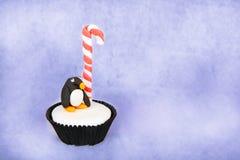 Julpingvinmuffin med den vita fondantglasyren på kaka Arkivbilder