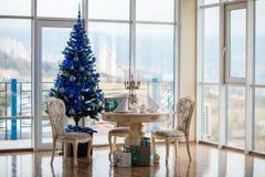 Julplats med en julgran, gåvor, en tabell och stolar jullunch Arkivfoto
