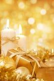 Julplats med guld- struntsaker, gåvan och stearinljus Arkivfoto