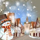 Julplats med hus i snö och gullig snögubbe Royaltyfri Bild