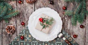 Julplattan med gåvan på träferiebakgrund med, sörjer kottar, röda garneringar royaltyfri fotografi
