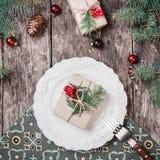 Julplattan med gåvan på träferiebakgrund med, sörjer kottar, röda garneringar, granfilialer royaltyfria bilder