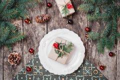 Julplattan med gåvan på träferiebakgrund med, sörjer kottar, röda garneringar, granfilialer arkivbild
